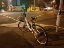 Abandoned dockless bike-sharing cycle at city intersection at ni Royalty Free Stock Photography