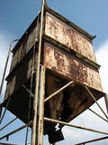 Abandoned Elevated Farm Tank. A view of a rusty, abandoned old elevated grain tank found on a rural farm Stock Photo