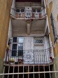 Abandoned empty apartment building with metal fence and balconies with iron railings and security bars on the door in mestre italy. An abandoned empty apartment stock image
