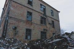 Abandoned fördärvade fabriksbyggnader med högen av det racka- ner på, rivning- och katastrofbegreppet Arkivbilder