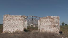 Abandoned fördärvade hangaren för tegelstenbyggnad i mitt av ett fält med gräs lager videofilmer