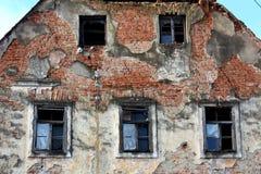 Abandoned fördärvade huscloseupen av brutna fönster och den stupade fasaden Arkivfoto