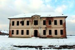 Abandoned fördärvade skolabyggnad som gjordes i det sista århundradet som täcktes med snö Arkivfoton