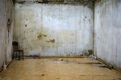 Abandoned fördärvar rummet en stol i hörnet Arkivbilder
