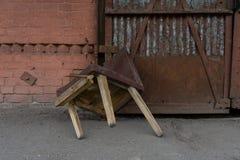 Abandoned förlägger Bruten trägammal stol på tegelstenväggen och rostig metallbakgrund royaltyfri bild