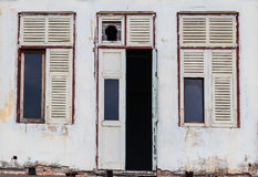 Abandoned Facade White Building with ruined Wooden Door and windows. Abandoned Facade White Building showing ruined Wooden Door and windows Royalty Free Stock Photography