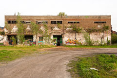 Abandoned factory building with graffiti on the wall. Royalty Free Stock Images