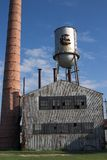 Abandoned factory building with water tower and chimney Royalty Free Stock Image