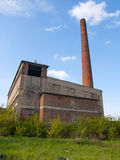 Abandoned factory with high chimney. Blue sky stock image