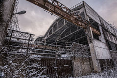 Abandoned factory. Abandoned industrial building with fence over cloudy sky in wintertime Stock Images