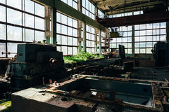Abandoned factory room with large windows and iron equipment royalty free stock images