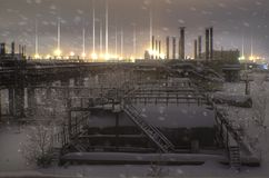 Abandoned factory, in winter, with barrels and pipes on the horizon glowing lights industrial areas, night landscape stock image
