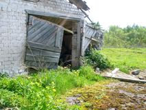 Abandoned farm barn. Doorway and side of an abandoned and rundown farm barn stock photo