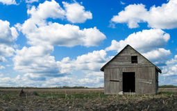 Abandoned Farm House. An old wooden farm house abandoned a long time ago, sitting under a blue partly cloudy sky Royalty Free Stock Image