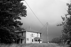 Abandoned Farm House Awaits a Downpour (B&W). An old, vandalized, abandoned farm house prepares to survive the high winds and drenching impending storm Stock Image