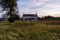 Abandoned Farm House at Sunset - Kentucky. An abandoned farm house viewed on a beautiful pink and blue hued sunset on a partly cloudy evening in central Kentucky stock photos