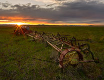 Abandoned farming equipment. On the field at sunset royalty free stock photography