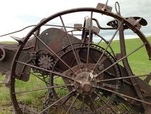Abandoned farming equipment. Side view of old farming equipment. You can see the wheel, gears and seat . Probably early 1900s. Located in western plains of Royalty Free Stock Images