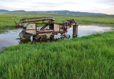 Abandoned farming equipment in water. Stock Photo
