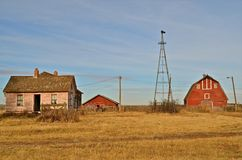 Abandoned Farmstead. An old abandoned farmstead with a wind mill, several barns and house remain only as memories Royalty Free Stock Image