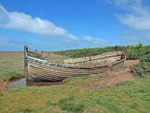 Abandoned fishing boat. The wreck of an abandoned fishing boat on the salt marshes at Blakeney Norfolk England Stock Photo