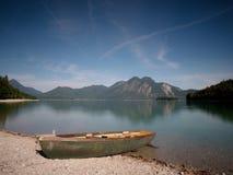 Abandoned fishing boat on bank of Alps lake. Morning lake royalty free stock photography