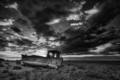 Abandoned fishing boat on beach landscape at sunset black and wh. Abandoned fishing boat on shingle beach landscape at sunset black and white Royalty Free Stock Photo