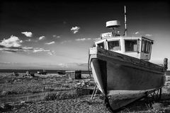 Abandoned fishing boat on beach landscape at sunset black and wh. Abandoned fishing boat on shingle beach landscape at sunset black and white Stock Image