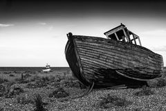 Abandoned fishing boat on beach landscape at sunset black and wh. Abandoned fishing boat on shingle beach landscape at sunset black and white Royalty Free Stock Image