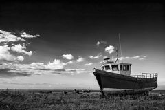 Abandoned fishing boat on beach landscape at sunset black and wh. Abandoned fishing boat on shingle beach landscape at sunset black and white Royalty Free Stock Images