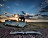 Abandoned fishing boat on beach landscape at sunset conceptual b. Abandoned fishing boat on shingle beach landscape at sunset conceptual book image Stock Images