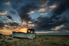 Abandoned fishing boat on beach landscape at sunset. Abandoned fishing boat on shingle beach landscape at sunset Royalty Free Stock Photos