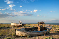 Abandoned fishing boat on beach landscape at sunset Stock Images