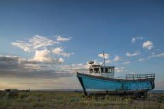 Abandoned fishing boat on beach landscape at sunset Stock Images