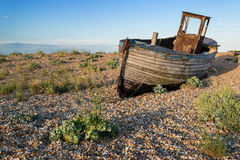Abandoned fishing boat on beach landscape at sunset. Abandoned fishing boat on shingle beach landscape at sunset Stock Image