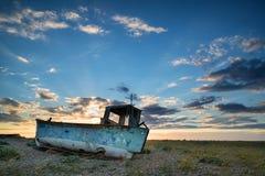 Abandoned fishing boat on beach landscape at sunset Stock Image