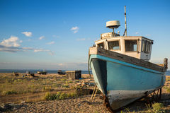 Abandoned fishing boat on beach landscape at sunset Stock Photography