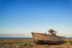Abandoned fishing boat on beach landscape at sunset. Abandoned fishing boat on shingle beach landscape at sunset Royalty Free Stock Image