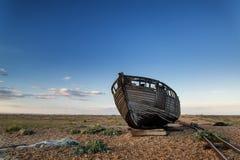 Abandoned fishing boat on beach landscape at sunset Stock Photos