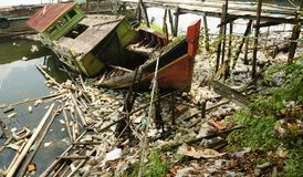 Abandoned fishing boat and lots of plastic waste royalty free stock image