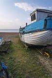 Abandoned fishing boat ruin on beach during lovely Summer mornin Stock Photos