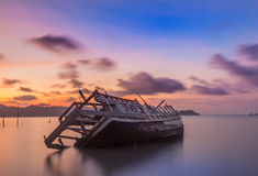 Abandoned fishing boat at sunset, Thailand. Stock Photos