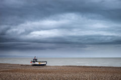 Abandoned fishing boats on shingle beach landscape in Winter Stock Photo