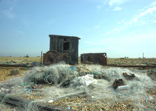 Abandoned Fishing huts and nets on beach. Royalty Free Stock Images