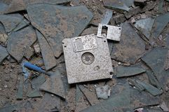 Abandoned floppy disc. Destroyed and abandoned vintage floppy disc. Forgotten technologies - 3.5 inch disk in plastic case on broken glass Royalty Free Stock Images