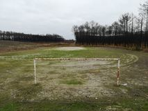 Old and abandoned soccer field with rusty goal post stock images