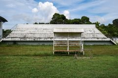 Abandoned football stadium and field with nobody. In stand and very bad grass, football field with poor ground conditions in the middle of nowhere Stock Image