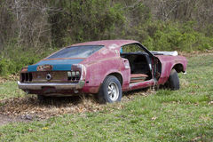 Abandoned 1969 Ford Mustang Fastback. A 1969 Ford Mustang fastback parked in a field awaiting restoration.  Missing a door, has mismatched parts, a diamond in Royalty Free Stock Photography
