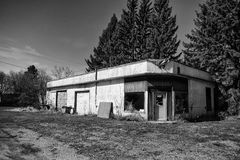 Abandoned garage surrounded by pine trees Stock Image