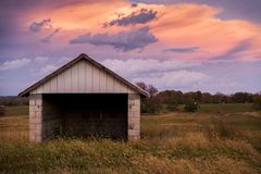 Abandoned Garage at Sunset - Kentucky. An abandoned garage viewed on a beautiful pink and blue hued sunset on a partly cloudy evening in central Kentucky Stock Images